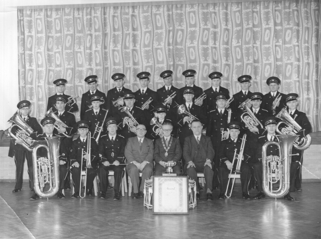 WGC Band - formal photo of band with members of WGC Council after winning the regional qualifying round of a national brass band competition. Image dated 1953/4 donated to the Welwyn Garden City Heritage Trust archive by Derek G during the 'Where Do You Think We Played?' project.