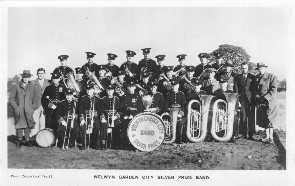 "WGC Band - Studio Lisa photograph (no.82) in postcard format of the ""WGC Silver Prize Band"". Derek donated this image to the Welwyn Garden City Heritage Trust archive during the 'Where Do You Think We Played?' project. Derek's father is pictured in the middle row - third uniformed player from the left."